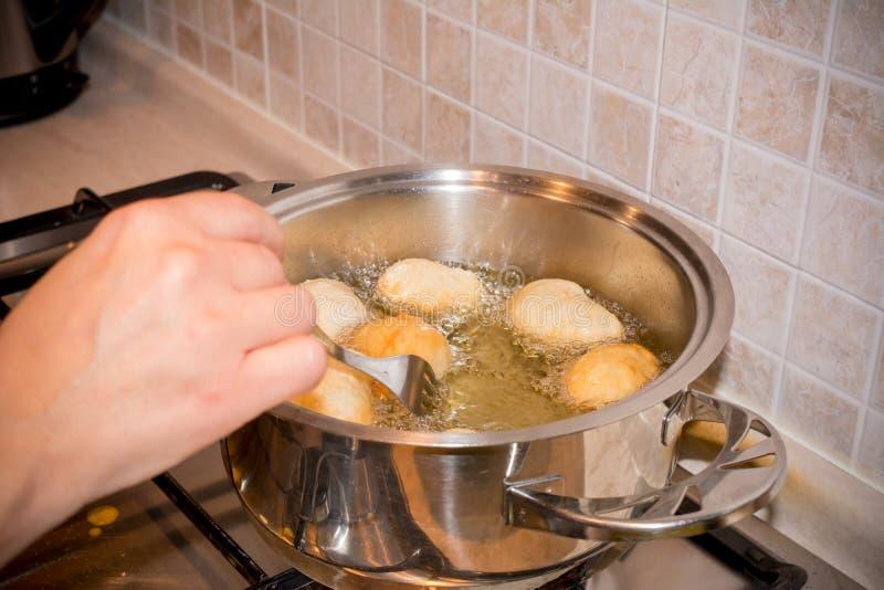 De handen van de vrouw dat het Aanpassen het Deeg Friying in een Pot tijdens t royalty-vrije stock afbeelding