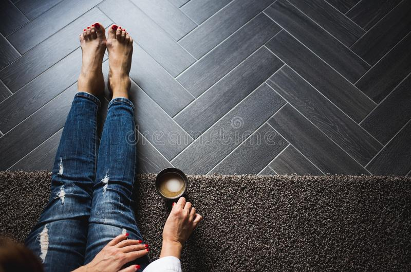 De handen van de vrouw met rode spijkers die kop van koffie op knieën houden terwijl het zitten op de bloem royalty-vrije stock afbeelding