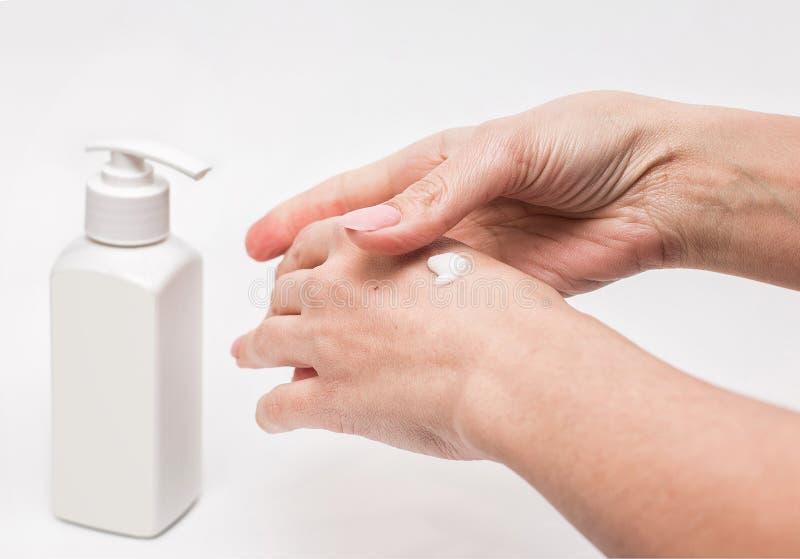 De handen van de vrouw met room Vrouw die vochtinbrengende cr?meroom op haar handen aanvragen zachte huid Gezondheid en schoonhei royalty-vrije stock foto