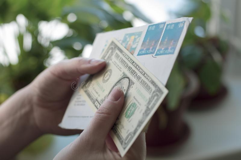 In de handen van vrouwen een envelop met zegels van Hong Kong en bankbiljet stock foto's