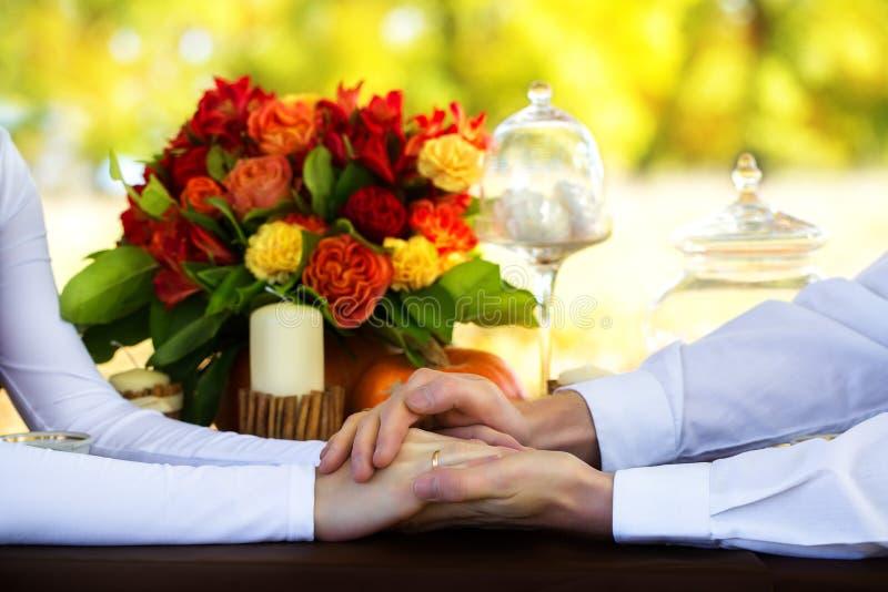 De handen van vrouwen en van mannen met trouwringen bij een verfraaide lijst royalty-vrije stock fotografie