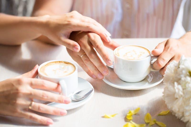 De handen van vrouwen en van mannen met trouwringen, bij wi van de koffielijst royalty-vrije stock foto's