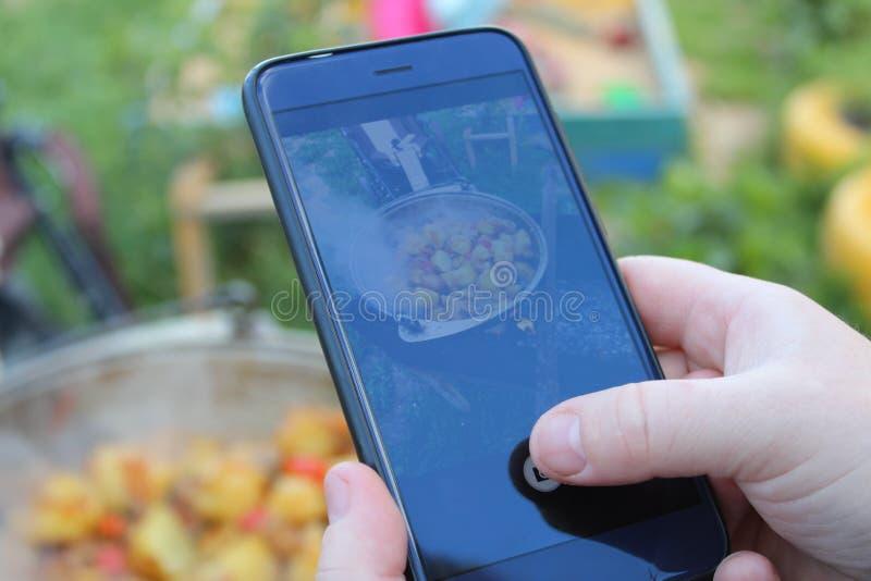 De handen van vrouwen houden de telefoon en nemen beelden van voedsel stock foto's