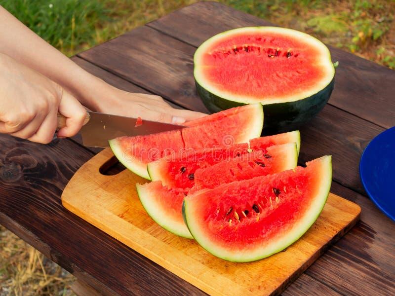 De handen van vrouwen met een mes in plakken van rijpe watermeloen op een houten lijst worden gesneden die stock foto's