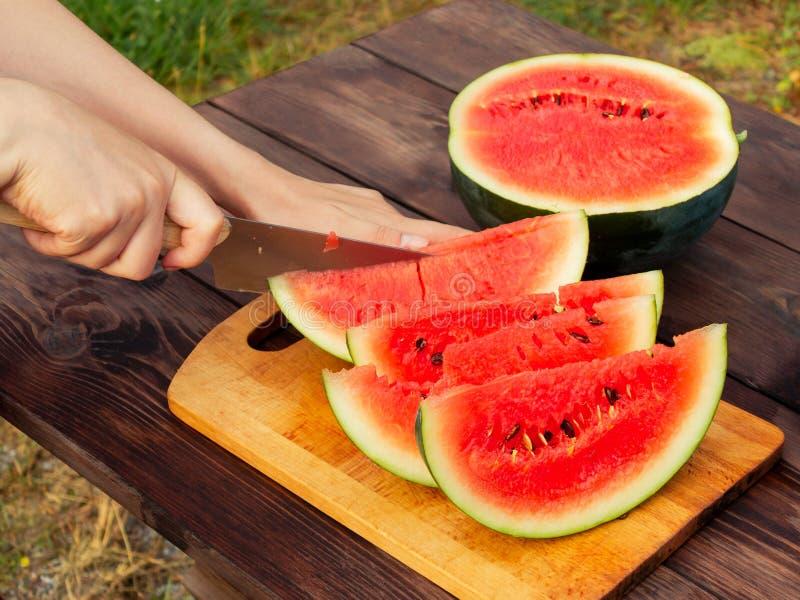 De handen van vrouwen met een mes in plakken van rijpe watermeloen op een houten lijst worden gesneden die royalty-vrije stock afbeelding
