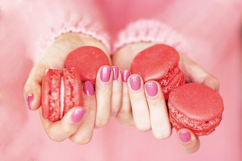 De handen van vrouwen met een mooie roze manicure stock fotografie
