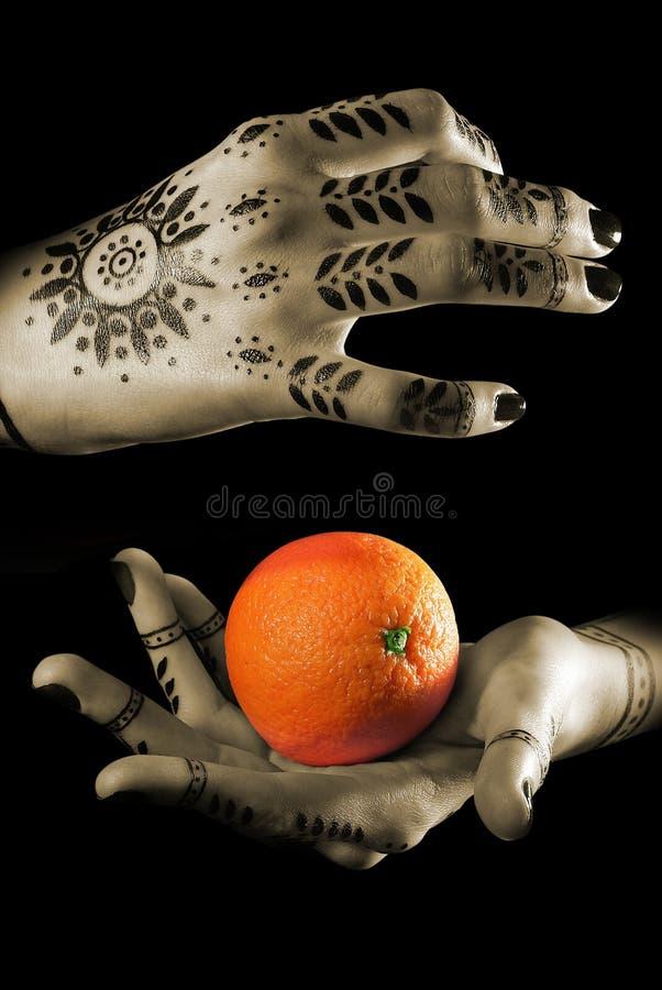 De handen van vrouwen met sinaasappel royalty-vrije stock afbeelding