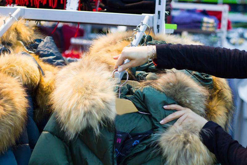 De handen van vrouwen raken de hangers met warme jasjes in de boutique stock foto