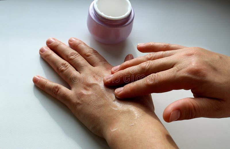 De handen van vrouwen smeren handen met bevochtigende room royalty-vrije stock afbeelding