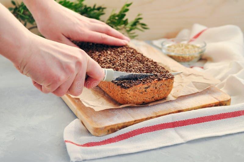 De handen van vrouwen snijden met een mes een stuk van eigengemaakt veganistbrood op een zuurdeeg van groen boekweit met lijnzaad royalty-vrije stock fotografie