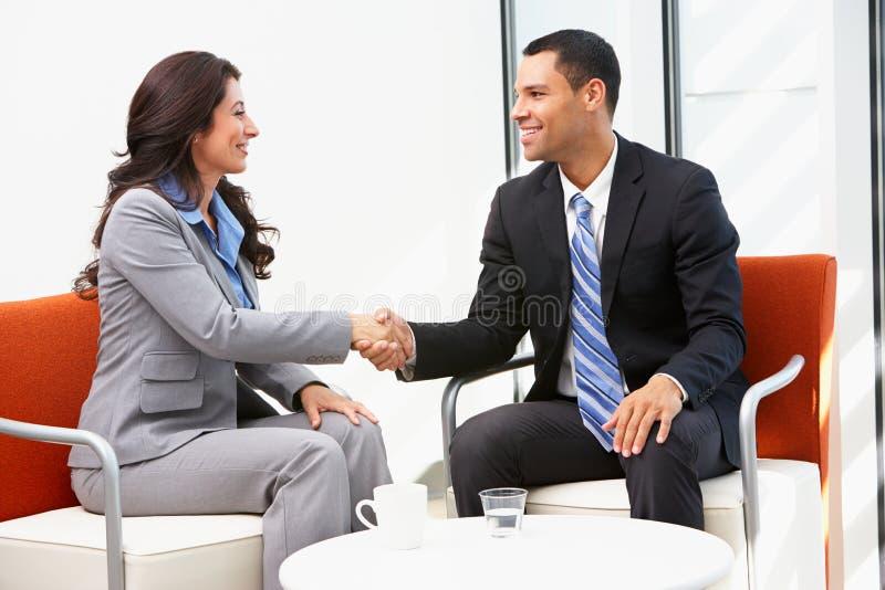 De Handen van zakenmanand businesswoman shaking na Vergadering royalty-vrije stock afbeelding