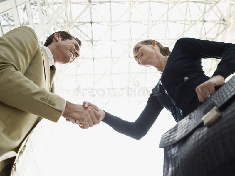 De Handen van zakenmanand businesswoman shaking tegen Plafond royalty-vrije stock afbeelding
