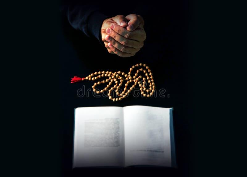 De handen vouwden in gebed over een Heilige Bijbel stock fotografie