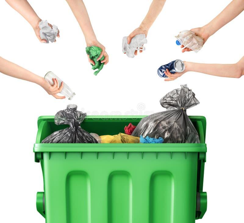 De handen werpen huisvuil in een vuilnisbak op een wit stock afbeeldingen