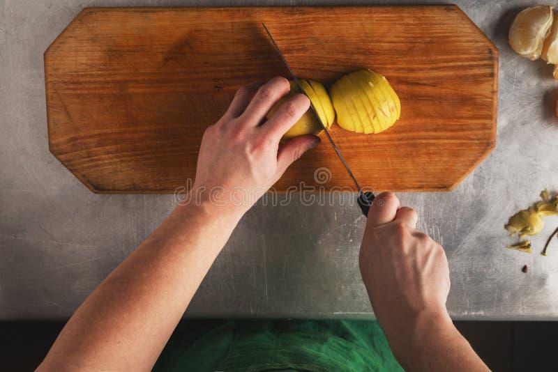 De handenschil en hakt de appel vruchten - appel en keukenmes op houten scherpe raad Hoogste mening over keukenlijst stock afbeelding