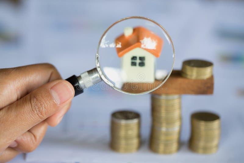 De handgreep een vergrootglas die naar een huis, Lening voor onroerende goederen zoeken of bespaart geld voor koopt een huis aan  stock foto's