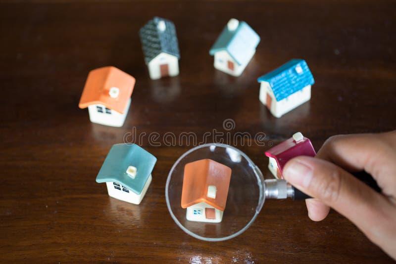 De handgreep een vergrootglas die naar een nieuw huis, Lening voor onroerende goederen zoeken of bespaart geld voor koopt een hui stock fotografie