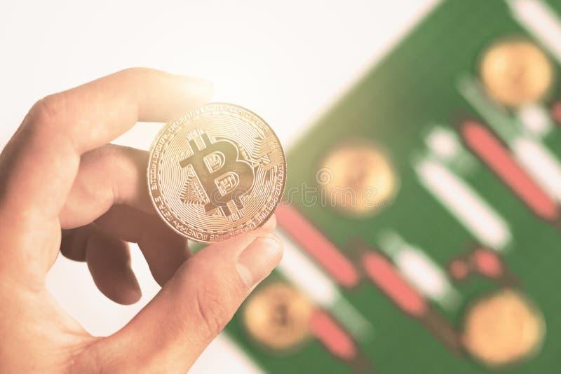 De handholding bitcoin met achtergrondkandelaargrafiek maakt van kleurendocument wit en rood stock afbeelding
