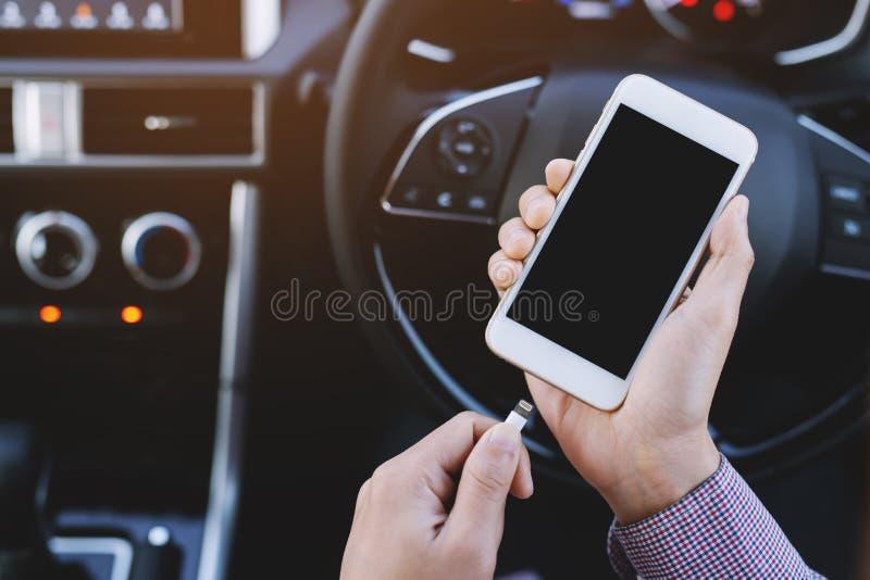 de handholding laadt de batterijtelefoon in auto stock foto