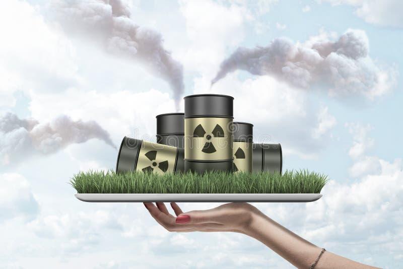 De de handholding van de vrouw ipad met het groene gras groeien op het scherm en stapel van radioactief afvalvaten op het die bet stock fotografie