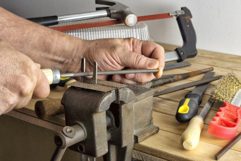 De handhulpmiddelen liggen op een werkbank in de workshop stock foto's