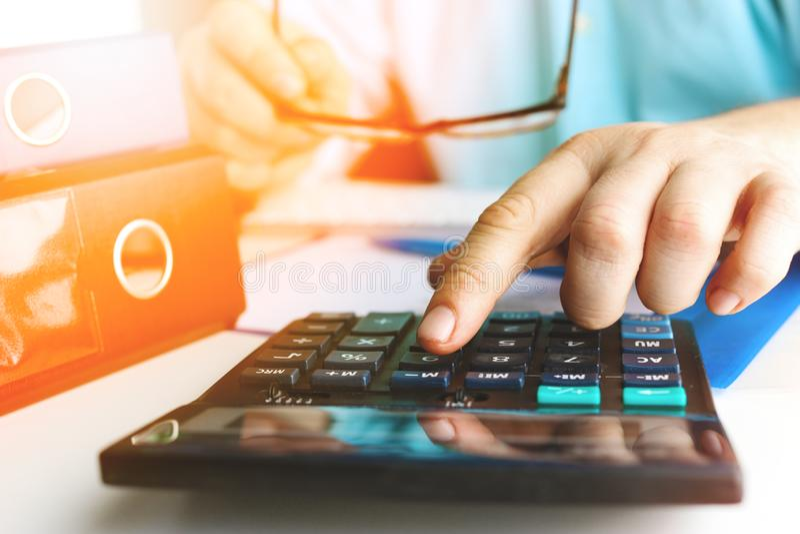 De handmens die financiën doen en berekent op bureau over kosten thuis bureau gestemd stock afbeeldingen