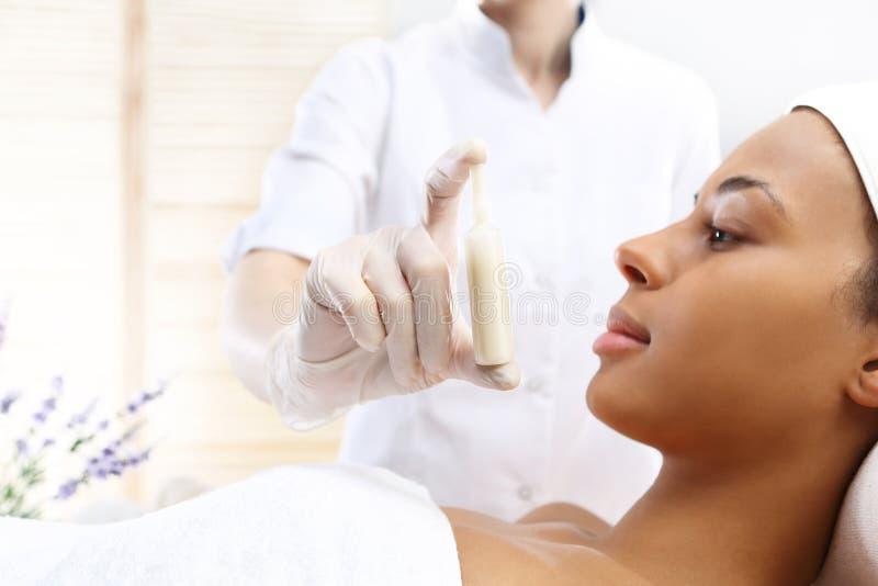 De handschoonheidsspecialisten toont een ampul met een kosmetische voorbereiding stock afbeelding
