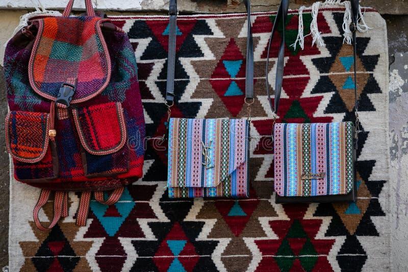 De handtassen van vrouwen van het met de hand gemaakte wolstof hangen op de achtergrond van hand-woven tapijt met traditionele pa stock foto