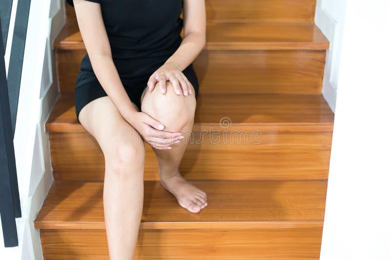 De handvrouw wat betreft haar benen en het hebben van een kniepijn, Vrouwelijk gevoel putte en pijnlijk uit royalty-vrije stock afbeeldingen