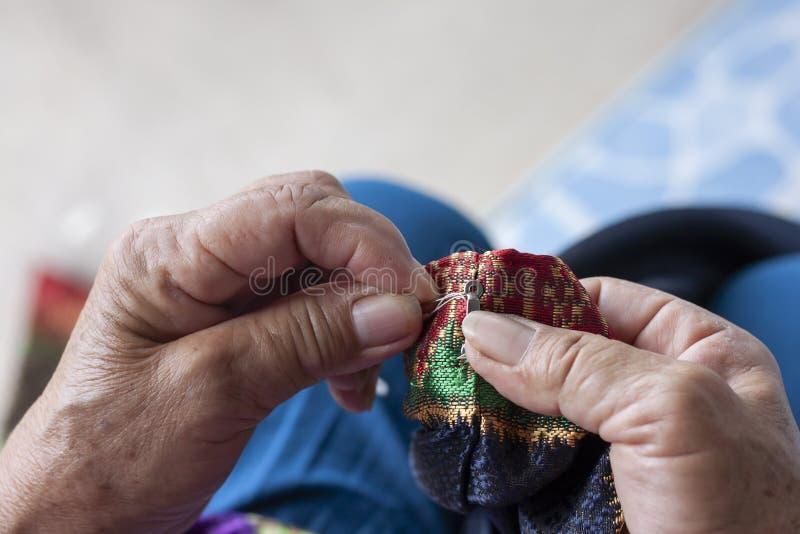 De handvrouwen naaien haken voor het vastmaken van kleren stock foto's