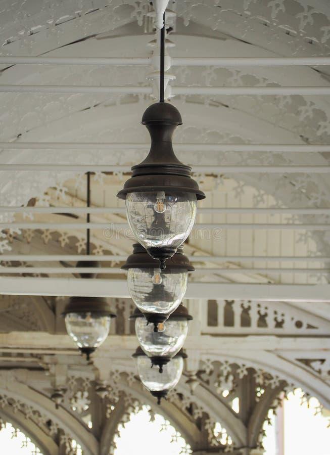 De hangende lantaarns in witte houten colonnade Karlovy variëren bohemen Tsjechische Republiek Symmetrische hangende ouderwetse s stock afbeeldingen