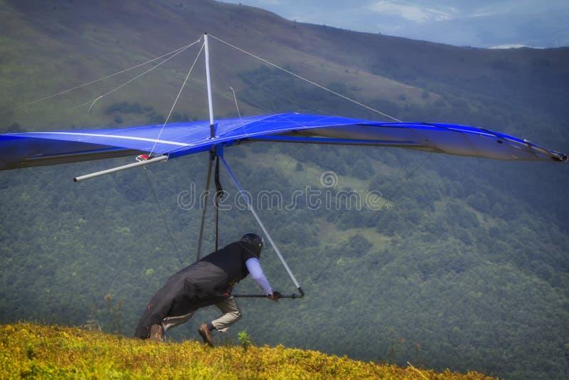De Hanggliderstart een atleet met een blauwe deltavlieger treft te beginnen voorbereidingen stock afbeelding