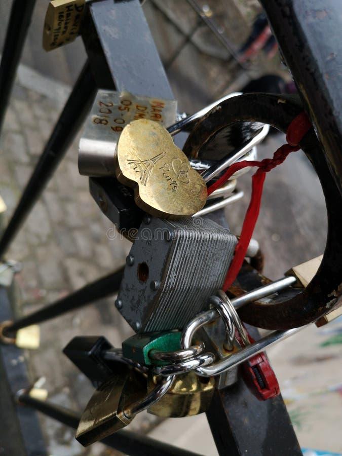 De hangsloten van liefdesloten in bijlage aan de brug in Parijs frankrijk stock foto
