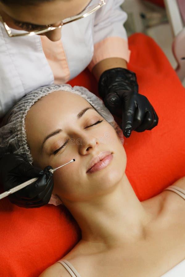 De hardwarekosmetiek De schoonheidsspecialist leidt reinigend gezicht van vrouw anti-veroudert behandelingen Geschoten van manicu royalty-vrije stock fotografie