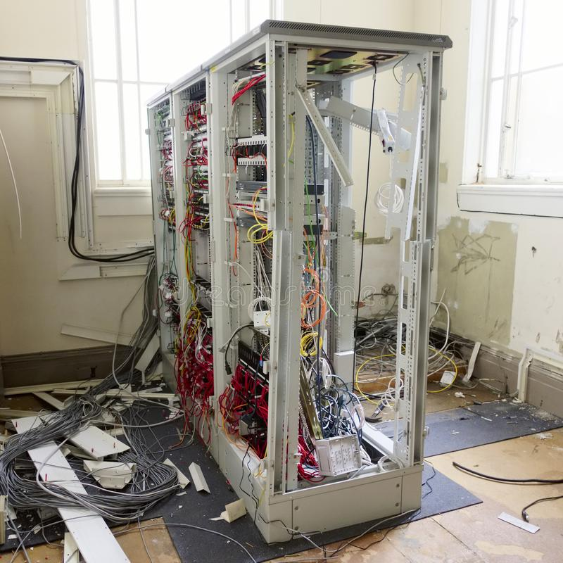 De hardwarerek van het serverkader en losse kabels in communicatie die ruimte in de verlaten bureaubouw wordt verwijderd stock foto