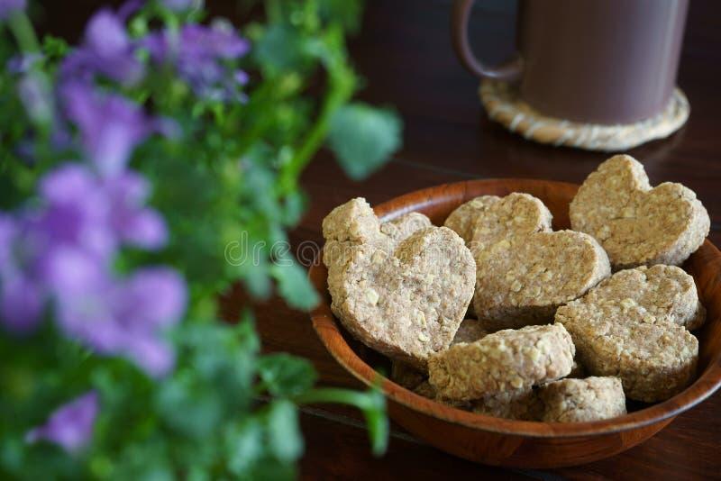 De hart-vormige Bloemen van de de mok Bruine lijst van haverkoekjes Bruine stock afbeelding