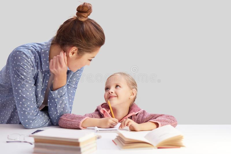 De hartelijke jonge moeder helpt haar weinig dochter met het doen van huistaak, stelt bij wit bureau met notitieboekje en handboe stock afbeeldingen