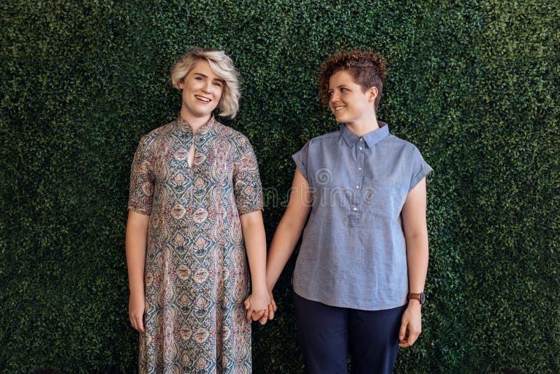 De hartelijke lesbische handen van de paarholding tegen een bladmuur buiten stock foto's