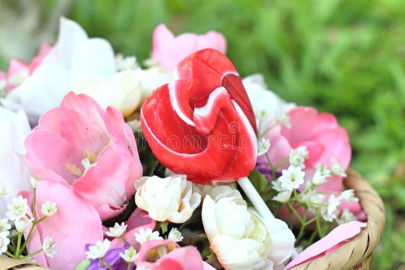 De harten van suikergoedvalentijnskaarten en kunstbloemen stock foto