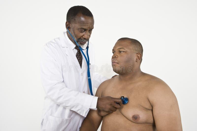 De Hartslag van de Patiënt van artsenchecking an obese stock foto's