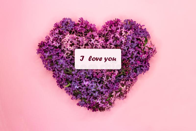 De hartvorm van purpere lilac bloemen met inschrijving I wordt gemaakt houdt van u op pastelkleur roze achtergrond die Het symboo stock fotografie
