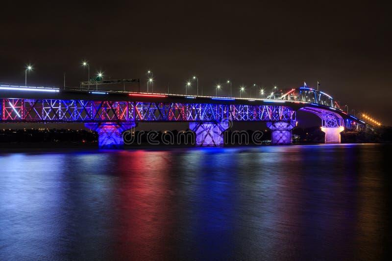 De Havenbrug van Auckland, Nieuw Zeeland, bij nacht met multicolored verlichting omhoog wordt aangestoken die stock afbeeldingen