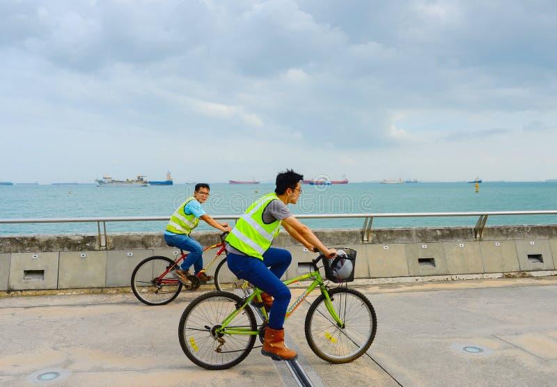 de havenschepen van Singapore van arbeidersfietsen royalty-vrije stock fotografie