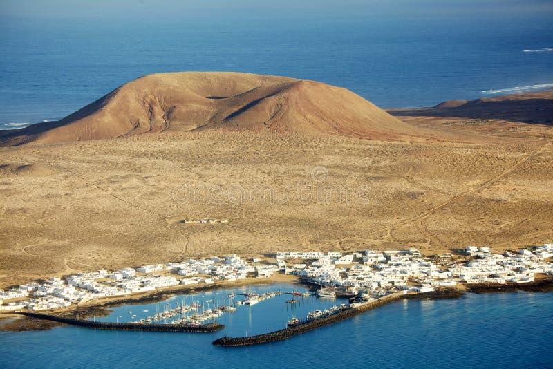 De havenstad van Caleta del Sebo van het naburige Eiland dat Lanzarote wordt gezien stock afbeeldingen