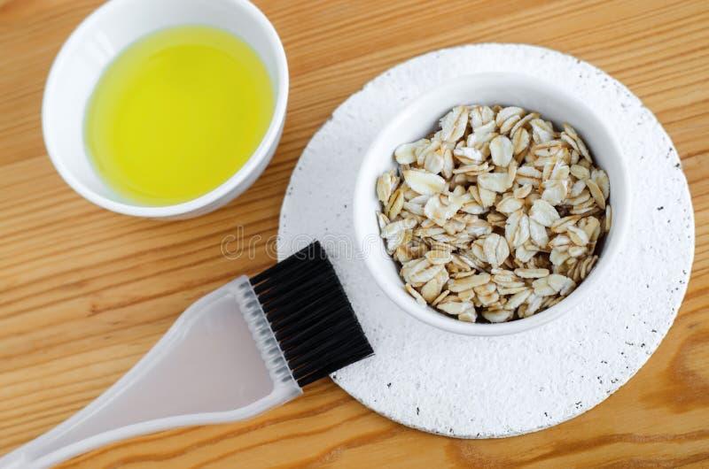 De haver schilfert en olijfolie in kleine ceramische kommen voor het voorbereiden van natuurlijke maskers af en schrobt Ingrediën royalty-vrije stock fotografie