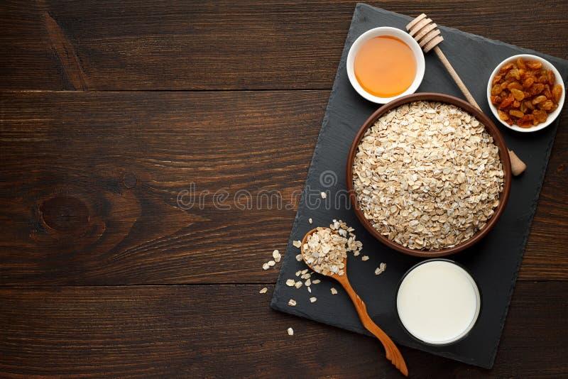 De haver schilfert op de kom en de honing, rozijnen, melk op leiraad en rustieke houten achtergrond af stock foto
