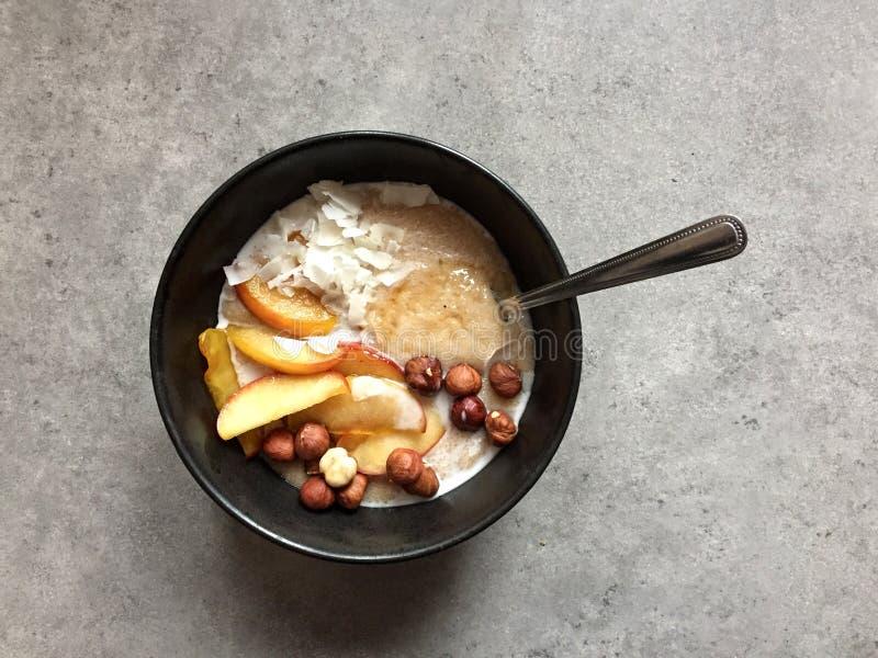 De havermoutpap van de veganistamarant met kokosmelk, hazelnoten en sautéed appelen stock foto