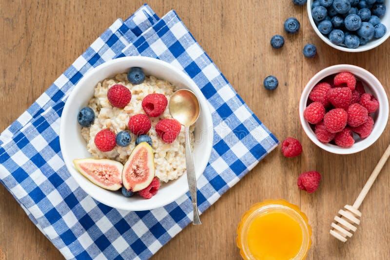 De Havermoutpap van het ontbijthavermeel met Vruchten Bessenhoning stock fotografie