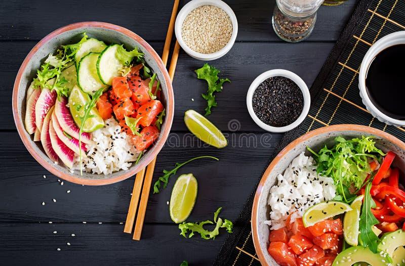 De Hawaiiaanse zalmvissen porren kom met rijst, avocado, paprika, komkommer, radijs, sesamzaden en kalk De kom van Boedha Het voe royalty-vrije stock afbeelding