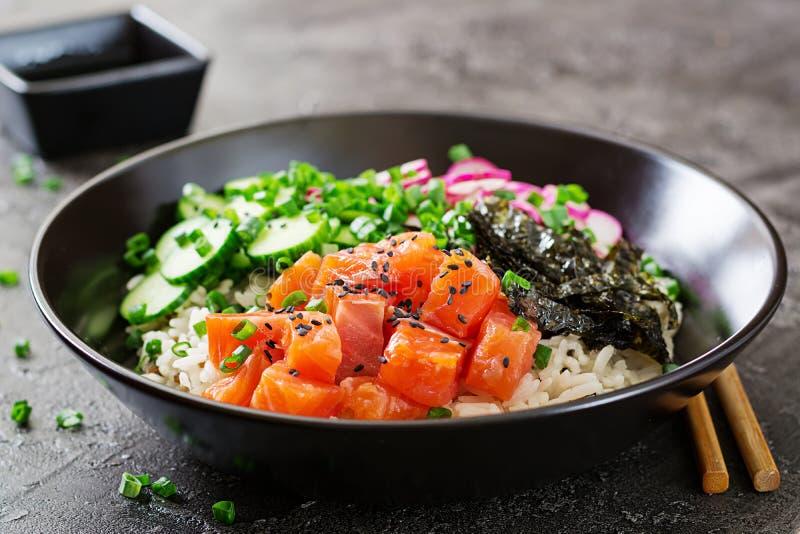 De Hawaiiaanse zalmvissen porren kom met rijst, radijs, komkommer, tomaat, sesamzaden en zeewieren royalty-vrije stock foto's